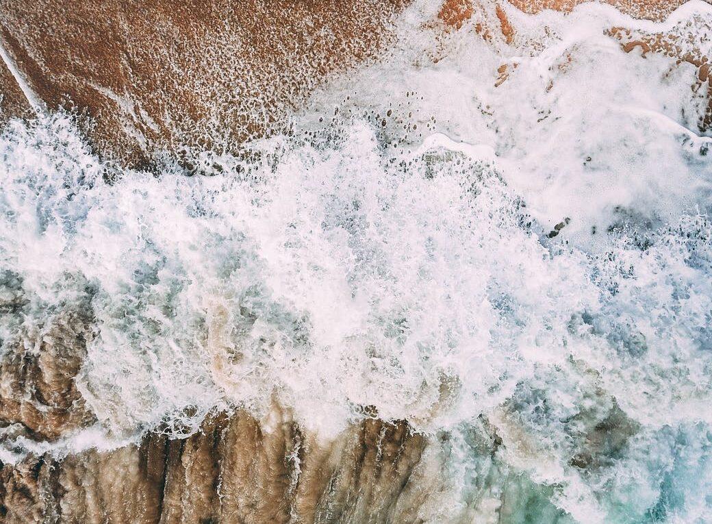 powerful foamy wave washing sandy coast