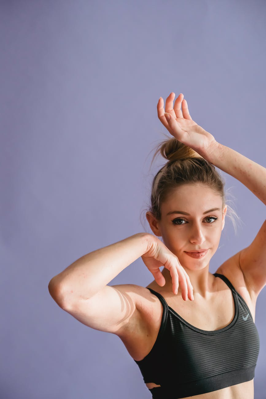 charming female dancing and looking at camera against purple background